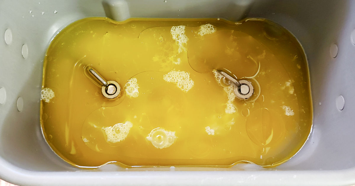Water, eggs, olive oil and apple cider vinegar in bread machine pan.