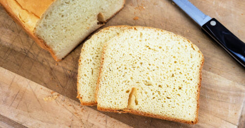 Two slices of gluten free bread next to freshly baked loaf on cutting board with bread knife.