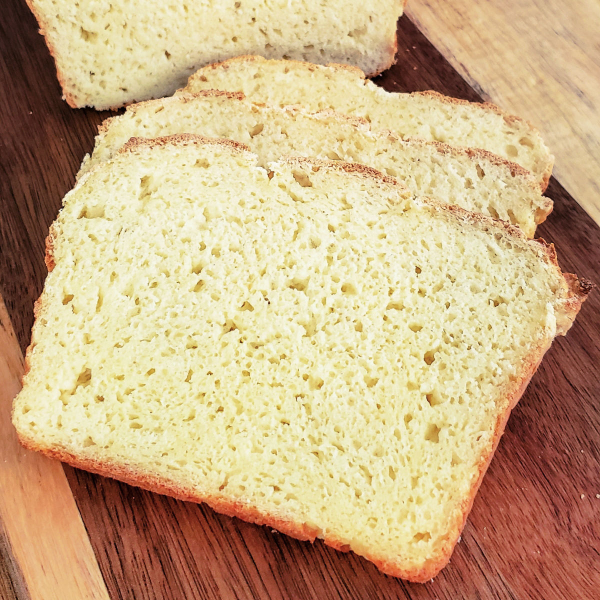 3 slices of homemade gluten free bread on cutting board.