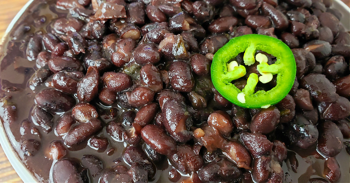 Close up of black beans cooked in an Instant Pot, topped with a jalapeno slice.