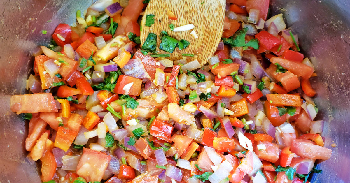 Tomato, garlic, jalapeno and cilantro being stirred into the onion and bell pepper mixture in the Instant Pot inner pan.