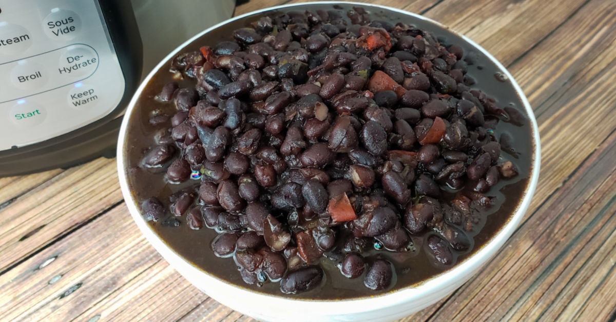 Black beans ladled from Instant Pot into a white serving bowl.