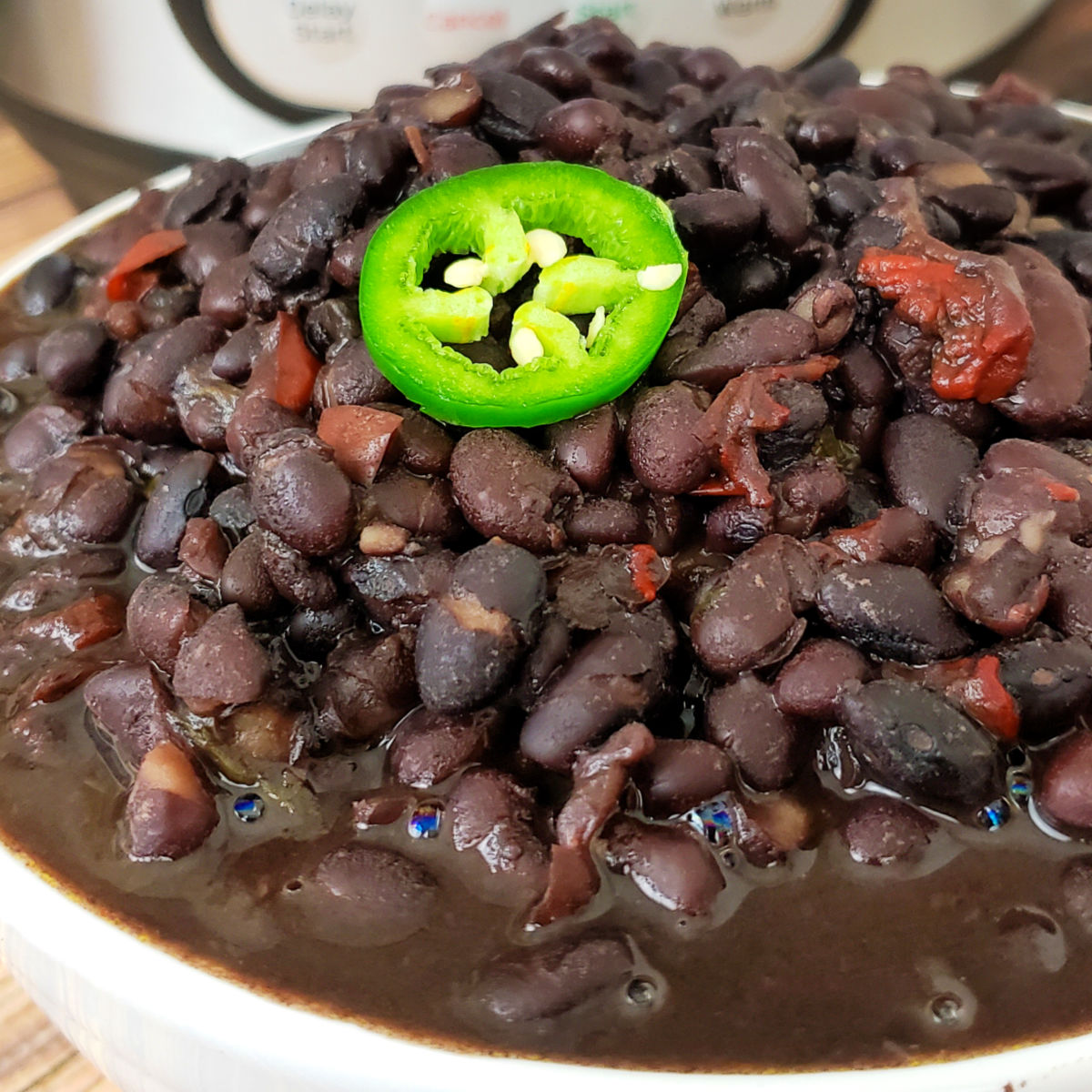 Black beans garnished with a jalapeno slice in a bowl with Instant Pot in background.