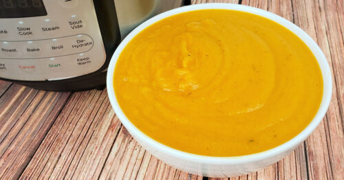 White bowl of butternut squash soup on table with the Instant Pot it was cooked in.