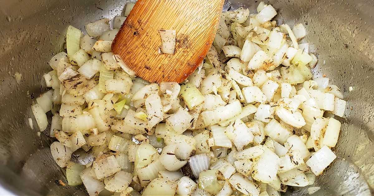 Sea salt, garlic powder, black pepper, sage and thyme being added to cooking onions and garlic in Instant Pot.