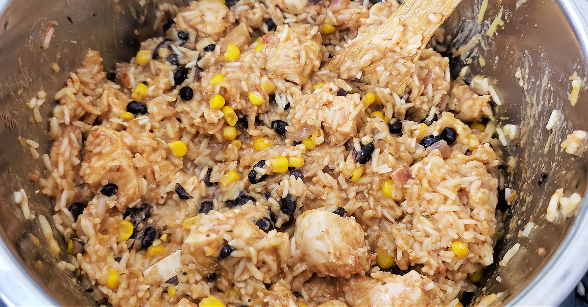 Bamboo spatula stirring cheese into chicken burrito bowls in Instant Pot inner pan.