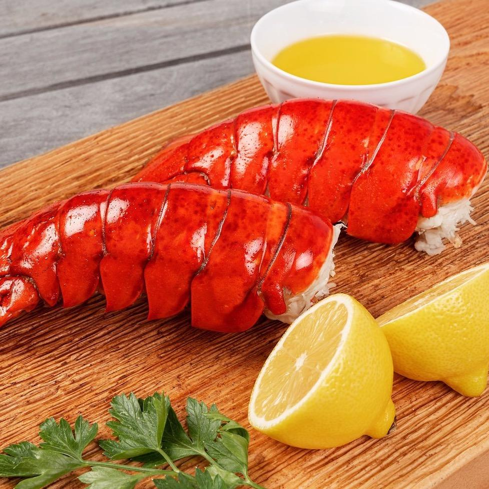 Two lobster tails on cutting board with lemon halves and butter.