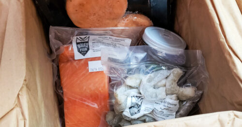 Wulf's Fish shipping box containing salmon, salmon burgers, trout burgers, shrimp and kelp beet kraut.