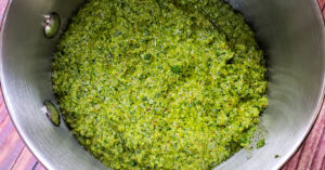 Cilantro pesto being warmed in a sauce pan.