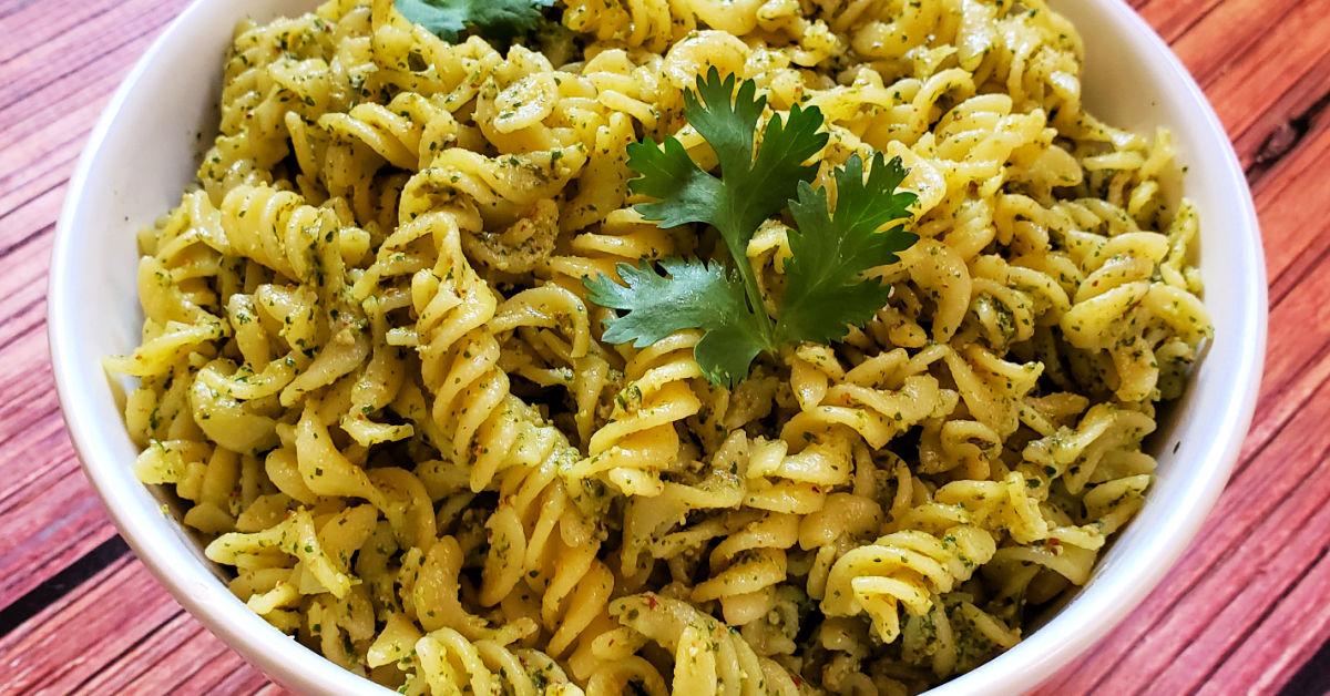 Cilantro pesto on gluten free pasta in white bowl.