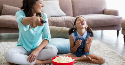 Little girl laughing and eating popcorn while watching a movie with her mom.