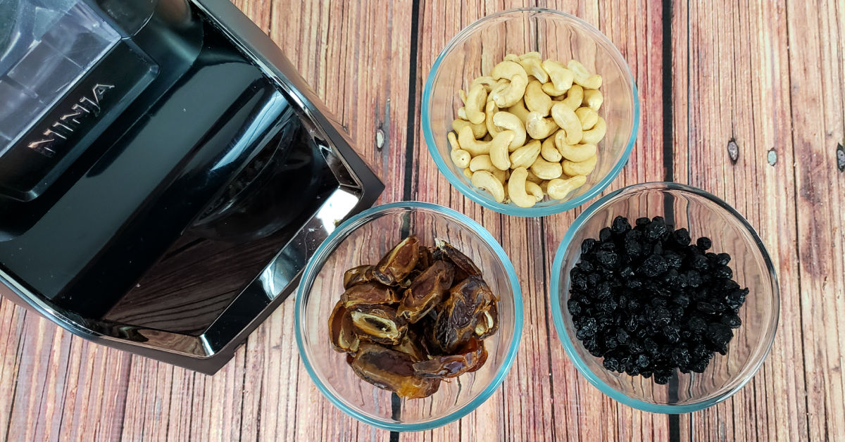 Cashews, pitted dates and dried blueberries in bowls with blender.