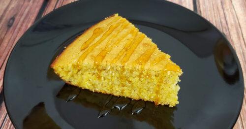Slice of gluten free cornbread drizzled in honey on a black plate.