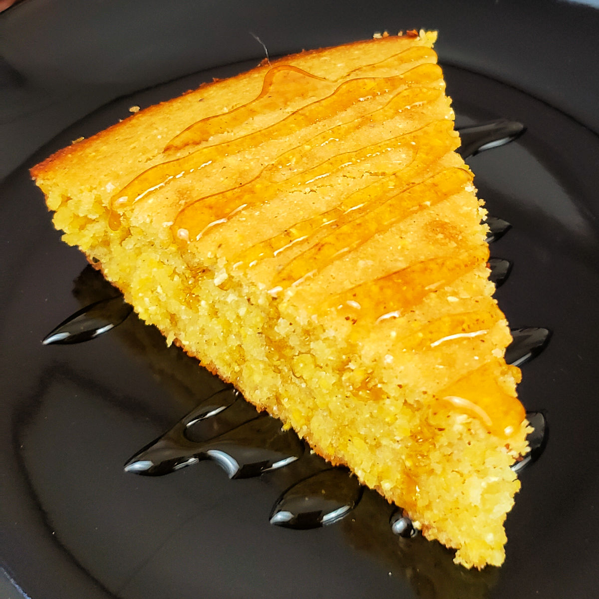 Slice of gluten free cornbread drizzled with honey on a black dessert plate.