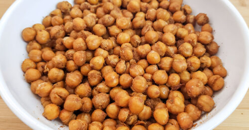 Roasted chickpeas in shallow white serving bowl.