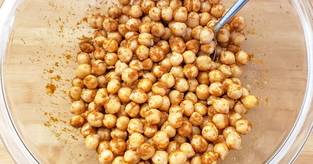 Taco seasoning being stirred into chickpeas in a bowl.
