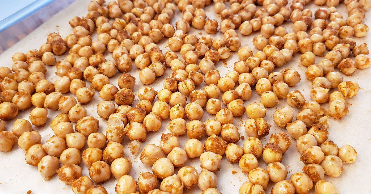Seasoned chickpeas laid out on sheet pan.